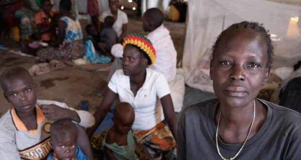 In the Democratic Republic of the Congo, Jeanette Buse Lasi, a widowed mother of four, sits with her children inside a communal shelter in an IDP camp in Bunia.